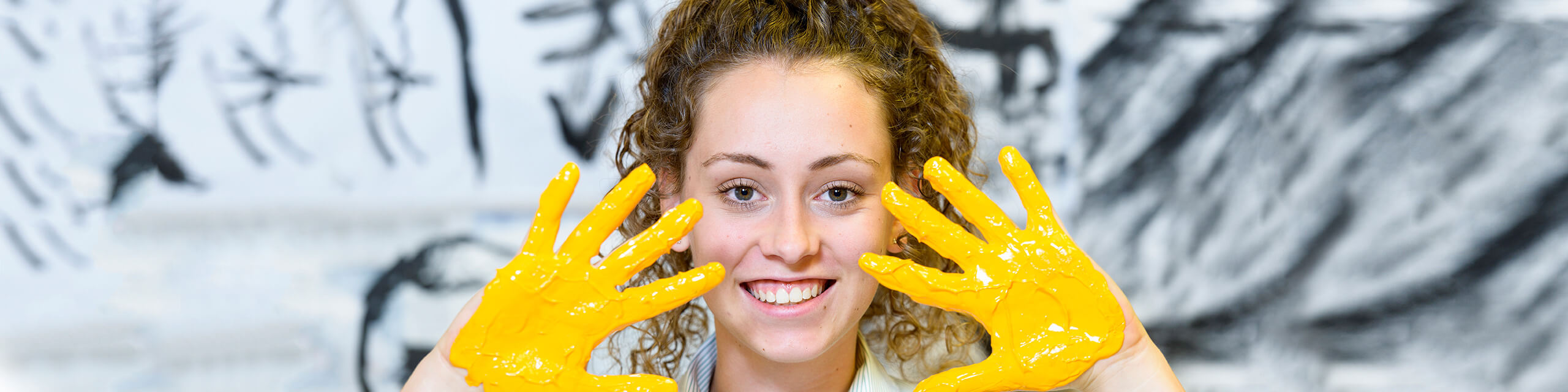 Art student with yellow paint on hands - Brighton Secondary School