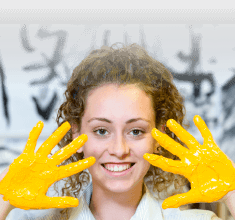 Art student with yellow paint on hands